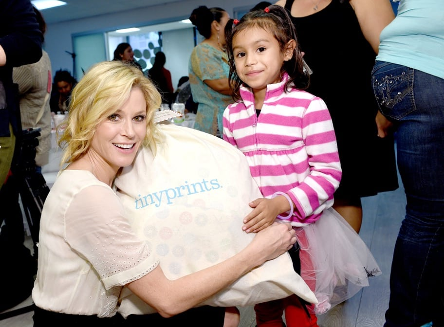 Actress Julie Bowen distributes a goodie bag filled with gifts to one of the guests of the Baby2Baby Nutcracker Party, presented by Tiny Prints. PHOTO BY STEFANIE KEENAN/GETTY IMAGES FOR BABY2BABY