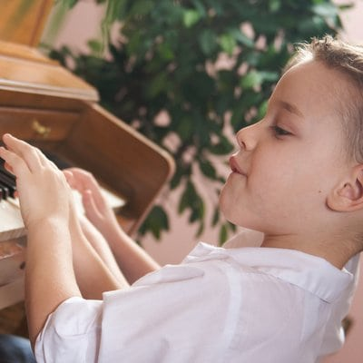 Brother and Sister Playing the Piano Together
