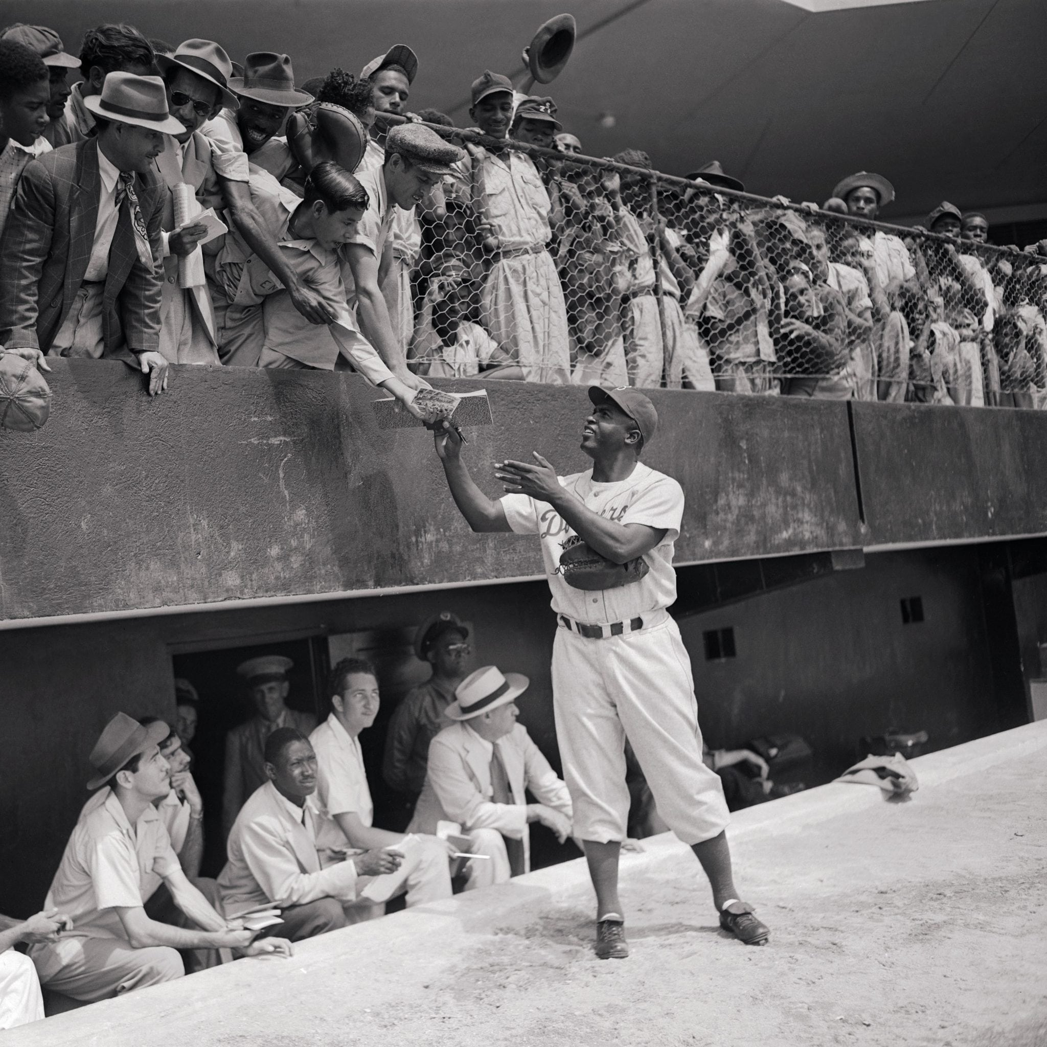 06 Mar 1948, Santo Domingo, Dominican Republic --- Original caption: On his first day of spring training with the Brooklyn Dodgers here, Jackie Robinson, Negro first baseman, proved a prime favorite with San Dominicans. He is shown here giving his autograph to some of the natives who watched the Dodgers workout at the Trujillo High School grounds. --- Image by © Bettmann/CORBIS