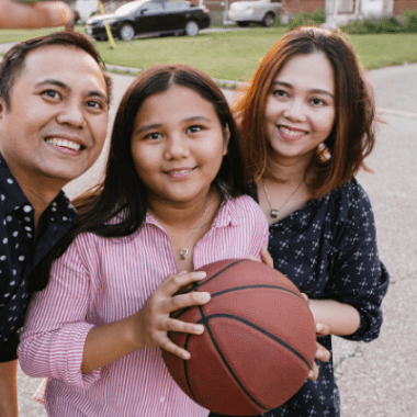 Young teen holding basketball is flanked by two adults. All are smiling into a camera for a selfie photo.