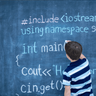 A boy writes coding instructions on a blackboard.